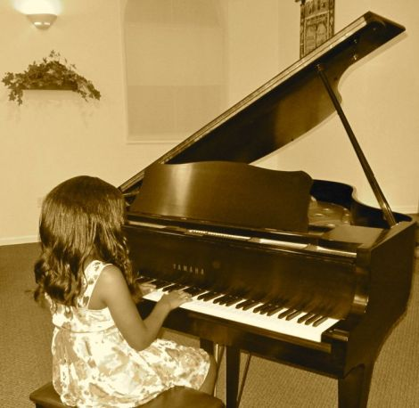 Image of a child playing the piano - Inspire your kids to practice and master a skill during the school year