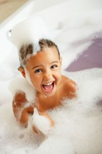 Image of girl washing hair in a bath tub