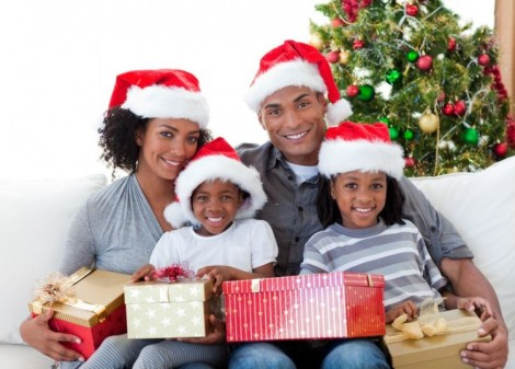 Image of African American family holding Christmas presents at home