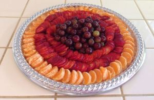 Fruit platter with tangerines, strawberries and grapes on a silver tray