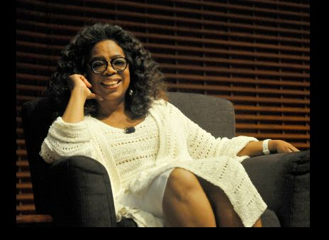 Photo of Oprah Winfrey with a smile sited on a chair.
