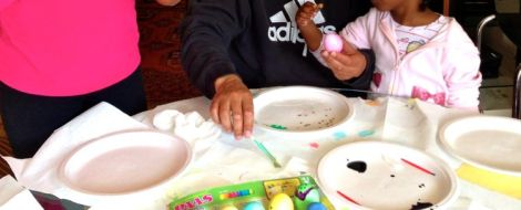 Image of little girl with her dad decorating Easter eggs