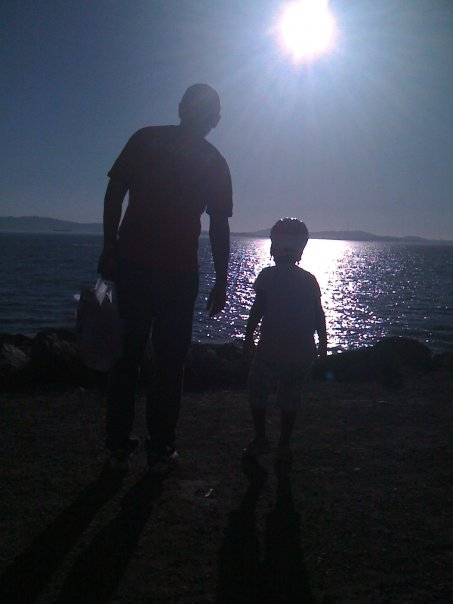 Silhouette of little girl and her dad at the beach