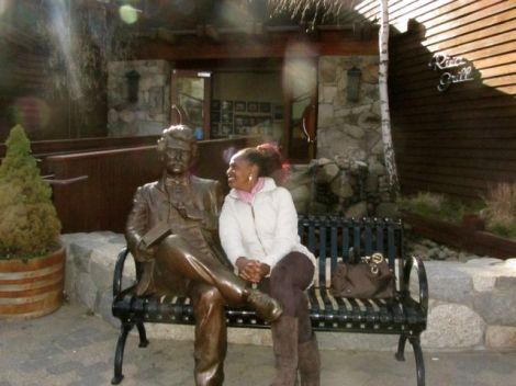 Woman sitting next to a statue