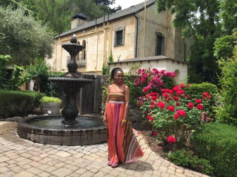 Image of happy woman standing in front of the Kenwood Spa fountain surrounded by beautiful red flowers