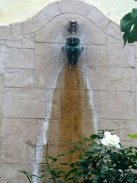 Image of lovely vase (from Tuscany) hoisted on wall with water running down the wall