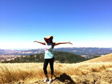 Woman celebrating at the top of her hiking trail