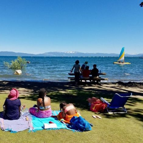 Image of two kids and one woman reading, writing and just chilling on Tahoe City beach