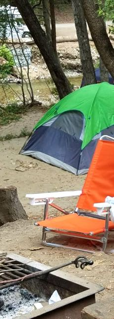 Image of tent and chair by the camp fire