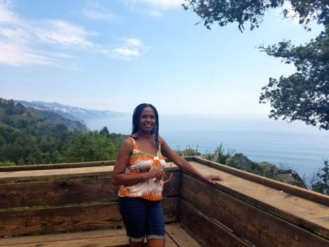 Image of woman posing on a balcony with a beautiful backdrop of the mountains and ocean