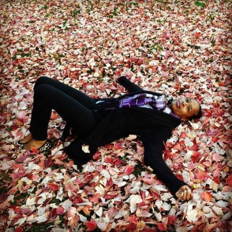 Image of woman laying in a bed of fall flowers