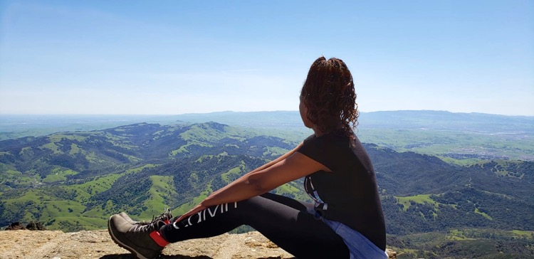 Image of woman sitting on a ledge overlooking to top of Mt. Diablo Summit