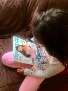 Image of 10 year old girl looking at a Cosmopolitan magazine with Normani on the cover