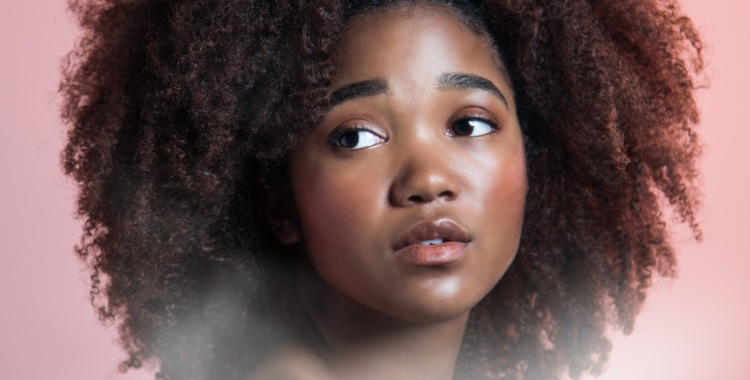 Photo of beautiful young black woman with flawless skin looking at the camera